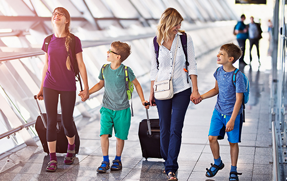 Family happily traveling together carrying luggage at the airport.