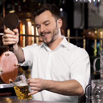 Guy pouring a beer from tap.